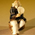 Miniature Figurine: Man Holding a Fan Sitting on a Rock – Blue Color – Fine Detail