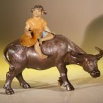 Miniature Figurine: Girl Riding on a Buffalo