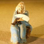Miniature Figurine: Man Holding a Fan Sitting on a Rock Light Blue Color – Fine Deta