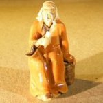 Miniature Figurine: Man Holding a Cup Sitting on a Rock – Light Brown Color – Fine Deta
